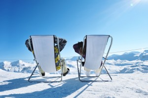 This is an image of two skiers in lounge chairs looking out at a sunny mountain range