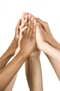 This is an image of multi-ethnic hands all coming together as one