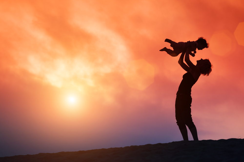 This is an image of a mother holding her child above her head at sunset