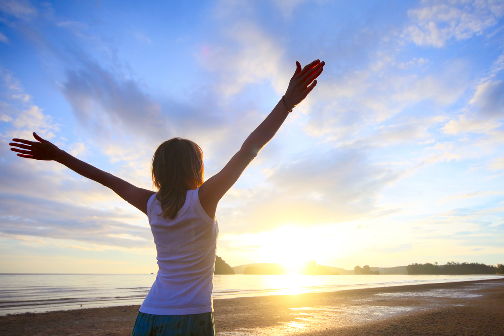 This is an image of a woman opening her arms to the horizon along the oceanfront