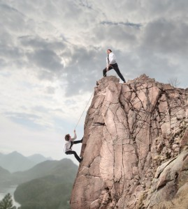 Image of two men on a mountain - one trying to pull the other one to the top.