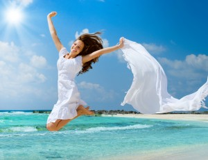 This is an image of a beautiful woman jumping for joy on the beach
