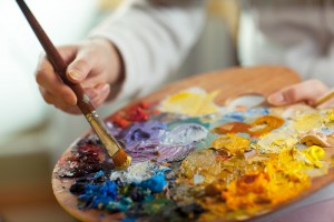 This is the image of a painter with their palette of beautiful an colorful oil paints