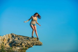 This is an image of a young women on the edge of cliff, tentatively looking down at how high up she is.