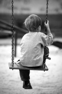 This is a black and white photograph of a little boy alone on a swing in the park