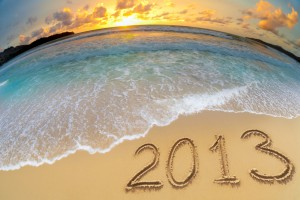 Fisheye lens view of the ocean with a beautiful sunrise with 2013 written in the sand