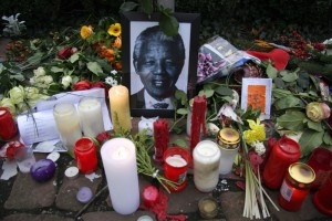 This is an image of candles surrounding a photo of Nelson Mandela
