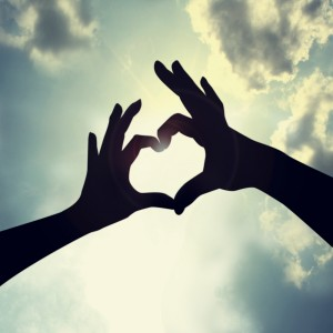 This is the image of two hands coming together with the sky in the background making the shape of a heart
