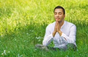 A man in a grassy field with the sun shining on him in a meditation pose